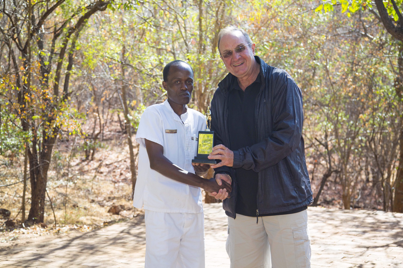 Dave Glynn handing over the inaugural trophy to Casper Mpofu the winner of the Victora Falls Safari Team for the 21km run